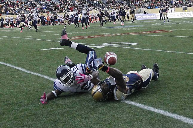Toronto Argonauts' Demetrice Morley (12) and Winnipeg Blue Bombers' Cory Watson (81) fight to bring down a pass in the dying seconds of the game.