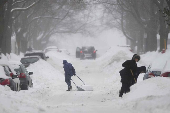 People clear snow from around their cars on a street in Montreal on Sunday.