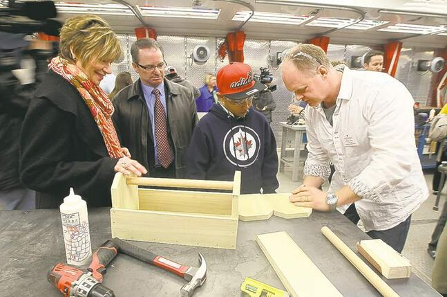 Nancy Allan, minister of education (left), watches as instructor Frank Jess demonstrates carpentry to Samuel Lopez.