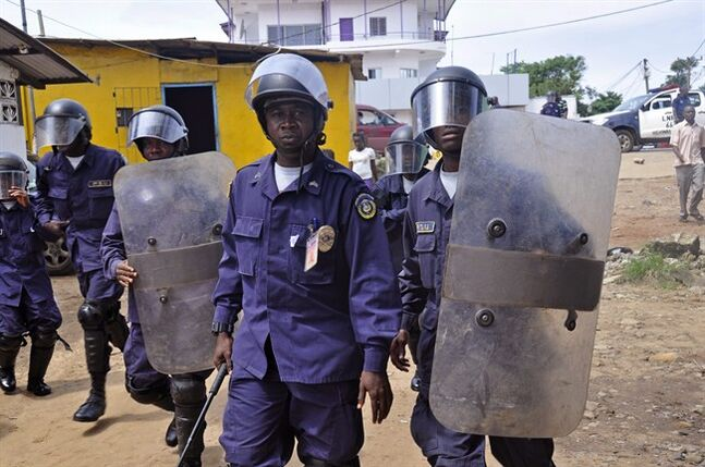 Liberia policemen, dressed in riot gear disperse a crowd blocking a main road, as they watch health workers deal with the body of a man suspected of dying from the Ebola virus, in the city of Monrovia, Liberia. Thursday, Aug. 14, 2014. Liberia faced an excruciating choice Thursday: deciding which handful of Ebola patients will receive an experimental drug that could prove either life-saving or life-threatening. ZMapp, the untested Ebola drug, arrived in the West African country late Wednesday. (AP Photo/Abbas Dulleh)