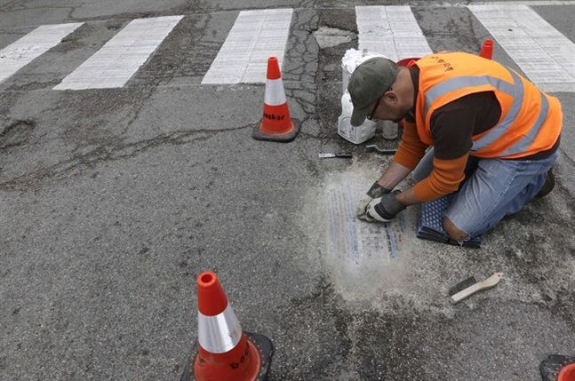 In this Tuesday, June 10, 2014 photo, mosaic artist Jim Bachor scrapes away cement to show a finished art piece in a filled pothole on a street in Chicago. Bachor has filled seven potholes around the city and marks each one with a mosaic piece. (AP Photo/Stacy Thacker)