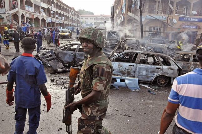 A Nigerian soldier, center, walks, at the scene of an explosion in Abuja, Nigeria, Wednesday, June 25, 2014. An explosion rocked a shopping mall in Nigeria's capital, Abuja, on Wednesday and police say at least over 20 people have been killed and many wounded. Witnesses say body parts were scattered around the exit to Emab Plaza, in the upscale Wuse 11 suburb. (AP Photo/Olamikan Gbemiga)