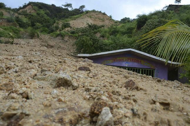 A small chapel is engulfed in rock and mud from a landslide triggered by heavy rains brought on by Tropical Storm Manuel on the outskirts of Acapulco, Mexico, Monday, Sept. 16, 2013.