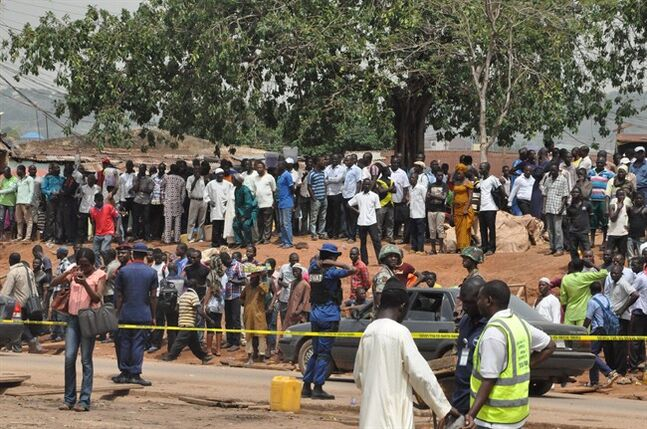 People gather at the site of a car bomb explosion in Abuja, Nigeria, Friday, May. 2, 2014. The death toll from a car bomb that exploded on a busy road in Nigeria's capital rose to more than a dozen overnight with dozens of people wounded, police said Friday from the city that within days hosts an international conference. The bomb was driven near a checkpoint where traffic built up, right across the road from a busy bus station where a massive explosion on April 14 killed dozens of people. (AP Photo/ Gbemiga Olamikan)