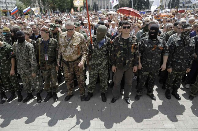 Pro-Russian fighters gather at a ceremony of take the oath of allegiance to the self-proclaimed Donetsk People's Republic, on Lenin square in the city of Donetsk, eastern Ukraine Sunday. Dozens of pro-Russian armed militiamen gathered on Lenin square in Donetsk on Sunday to take the oath of allegiance to the so-called Donetsk People's Republic after Ukrainian President Petro Poroshenko ordered his forces to cease fire Friday and halt military operations for a week.