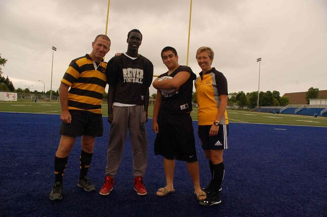 Rugby instructors Scott Harland (left) and Charlene Bakke (right) flank Kildonan-East Reiver players Deng Garang (second from left) and Brendan Proulx (second from right) after practice on Aug. 25.