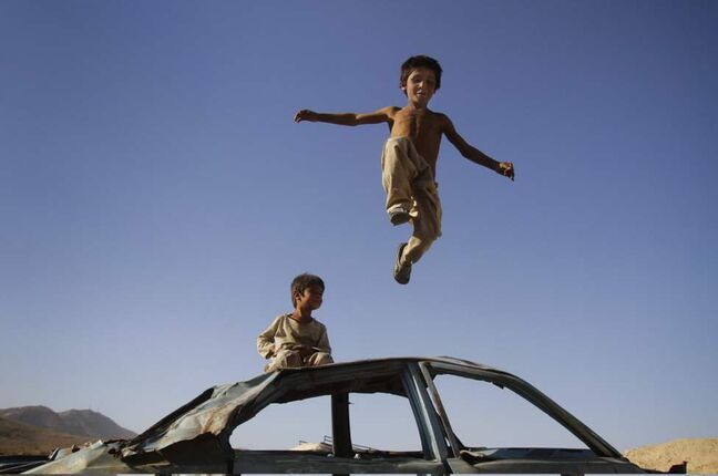 An Afghan boy jumps down from a vehicle in Kabul, Afghanistan. (AP Photo/Ahmad Jamshid)