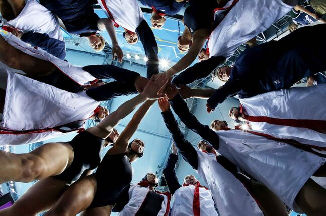 In this photo taken with a fisheye lens, Britain women's water polo players huddle before the seventh place water polo match at the 2012 Summer Olympics. (AP Photo/Julio Cortez)