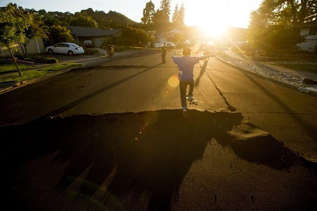 Skateboarder Bayley Lorenzen, 12, launches himself off buckled pavement in Napa, Calif., following an earthquake Sunday, Aug. 24, 2014. Officials in the city of Napa say 15 to 16 buildings are no longer inhabitable after Sunday's magnitude-6.0 earthquake, and there is only limited access to numerous other structures. (AP Photo/Noah Berger)