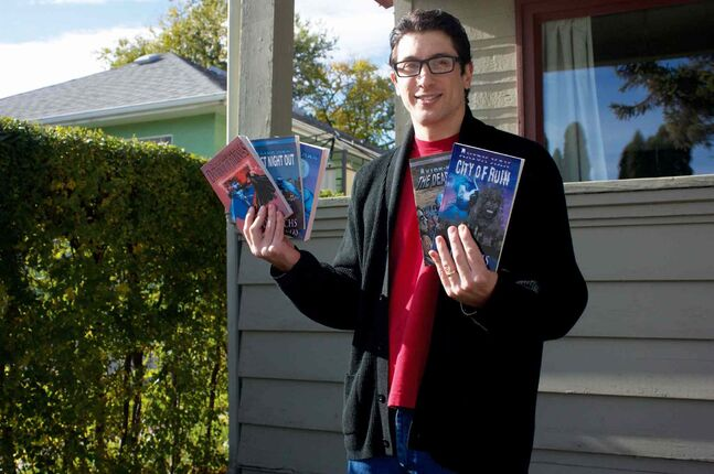 Novelist A.P. Fuchs is shown with some books from his Axiom-man series, which will have installments six and seven released at the upcoming Central Canada Comic Con.