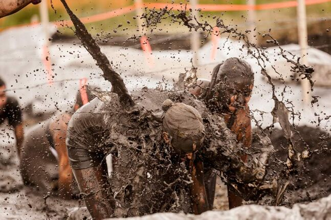 Dirty Donkey Mud Run participants are covered jn muddy water in a mud pit near the finish line Saturday morning.