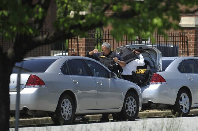 Law enforcement put on kevlar vests before searching the Paine College campus as it is on lockdown on Monday, May 5, 2014, in North Augusta, Ga. The second shooting in two days at a Georgia college Monday left a student with a life-threatening gunshot wound to the head and prompted authorities to pledge to bolster security at the school. (AP Photo/The Augusta Chronicle ,Jon-Michael Sullivan)