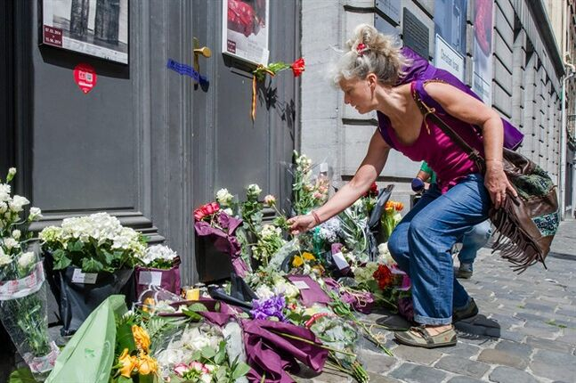 A woman lays flowers at the Jewish Museum in Brussels, Sunday May 25, 2014. Police stepped up security at Jewish institutions, schools and synagogues after three people were killed and one seriously injured in a spree of gunfire at the Jewish Museum in Brussels on Saturday. (AP Photo/Geert Vanden Wijngaert)