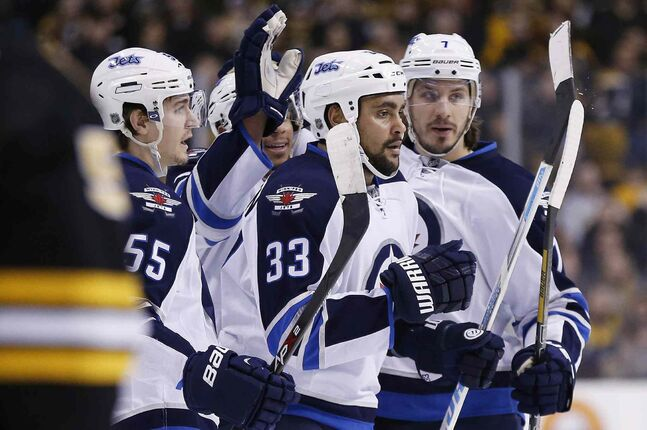 Winnipeg Jets' Dustin Byfuglien (33) celebrates his goal with teammates Mark Scheifele (55) and Keaton Ellerby (7) in the first period of an NHL hockey game against the Boston Bruins in Boston Saturday.