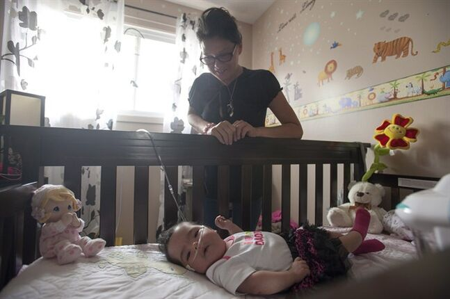 Josie Ledoux spends some time with her granddaughter Aurora in her deceased daughter's old bedroom in Prince Albert, Sask. on Saturday, July 12,2014. Ledoux's daughter Brandi Lepine was killed by an alleged drunk driver a year ago while pregnant with Aurora.