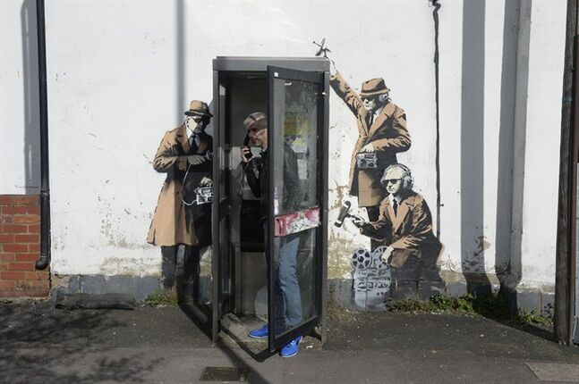 A new graffiti street art piece, suspected of being a Banksy, appeared in, Cheltenham England Monday April 14, 2014. Street artist Banksy may have struck again, leaving an espionage-themed graffiti artwork in the hometown of Britain's electronic spy agency. A stenciled artwork has appeared on a wall in the western England city of Cheltenham, depicting three figures in trench coats and trilbys snooping on a telephone booth. Cheltenham is home to GCHQ, Britain's electronic eavesdropping agency. The secretive organization found itself in the spotlight after some of its covert activities were revealed by former NSA contractor Edward Snowden. The work has not been claimed on Bansky's official website, but has many of the elusive artist's hallmarks, including the stenciled technique and vein of social commentary. (AP Photo/Ben Birchall/PA) Wire UNITED KINGDOM OUT NO SALES NO ARCHIVE