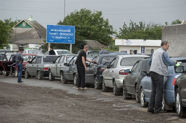 People stand at their cars waiting in line to leave Ukraine at the Ukrainian-Russian border checkpoint in Izvaryne, Friday, June 20, 2014. Some Ukrainians are leaving amid fighting in eastern Ukraine. Clashes between government forces and pro-Russia rebels flared ahead of the publication of a presidential peace plan that includes a unilateral cease-fire. (AP Photo/Evgeniy Maloletka)