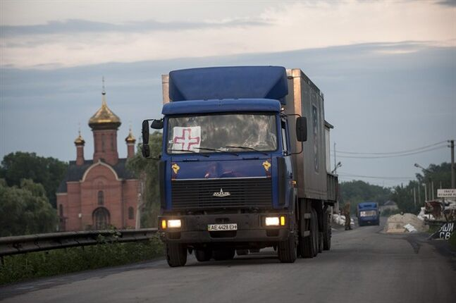 Trucks carrying the bodies of Ukrainian troops killed in a plane shot down near Luhansk, cross over to the Ukrainian side during a handover by pro-Russian fighters at a check point in the village of Karlivka near Donetsk, eastern Ukraine, Wednesday, June 18, 2014. The two sides managed to arrange a brief truce Wednesday evening in the eastern town of Karlivka to allow pro-Russian forces to hand over the bodies of 49 Ukrainian troops who died when the separatists shot down a transport plane bound for the airport in Luhansk last weekend. (AP Photo/Evgeniy Maloletka)