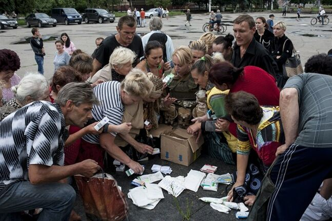 Local residents receive medicine in Slovyansk, eastern Ukraine, Sunday, July 6, 2014. Ukrainian troops on Saturday forced the rebels out of Slovyansk, a city of about 100,000 that had been the center of the fighting. The success there suggests that the government may finally be making gains in the months-long battle against the insurgency. (AP Photo/Evgeniy Maloletka)