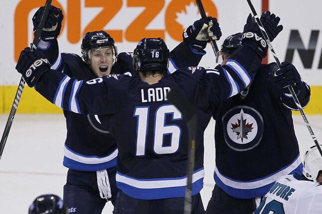 Winnipeg Jets' Bryan Little (18), Blake Wheeler (26) celebrates Andrew Ladd's (16) late game-tying goal against San Jose Sharks in third period NHL action in Winnipeg on Sunday, November 10, 2013.