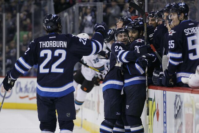 Winnipeg Jets' Chris Thorburn (22), Grant Clitsome (24) and Dustin Byfuglien (33) celebrate Byfuglien's goal against the San Jose Sharks.