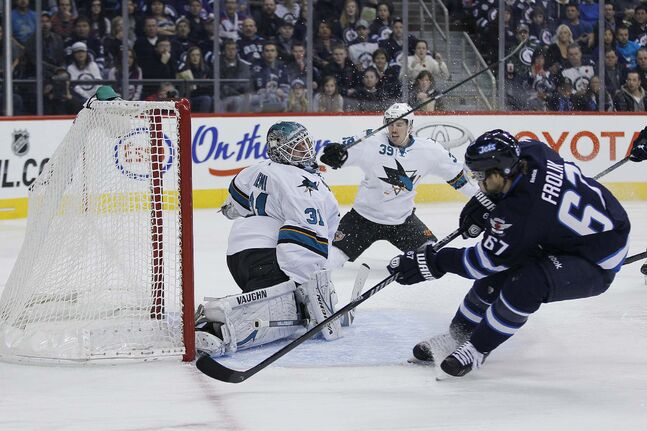 Winnipeg Jets' Michael Frolik (67) scores on San Jose Sharks' goaltender Antti Niemi (31) and Logan Couture (39) during second period action.