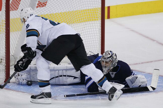 Winnipeg Jets' goaltender Ondrej Pavelec (31) stops the penalty shot by San Jose Sharks' Tommy Wingels (57) to win the game.