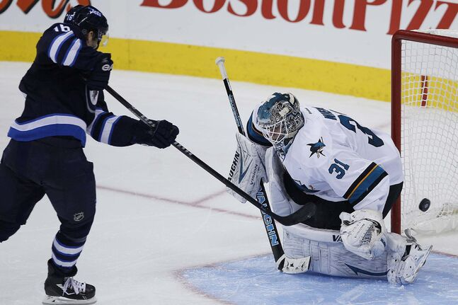Winnipeg Jets' Andrew Ladd (16) scores on San Jose Sharks' goaltender Antti Niemi (31) during penalty shots to take the lead.