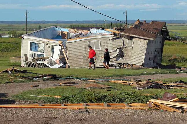 Residents of Sioux Valley Dakota Nation walk past a home that was blown off of its foundation by a suspected tornado Thursday evening. Two people were taken to hospital after the storm blew through the reserve during the supper hour.