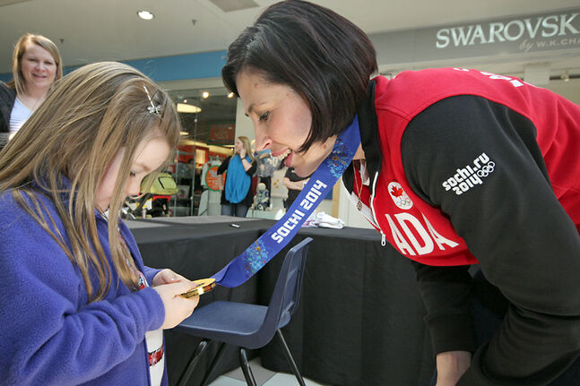 Six-year-old Ella Howe takes a close look at the gold medal won by Jill Officer at the 2014 Olympic Winter Games in Sochi, Russia.