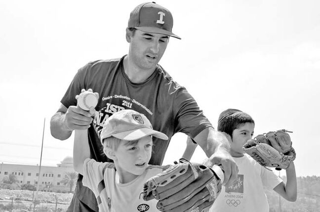 Baseball coach Nate Fish instructs an Israeli child during a 'Baseball for Beginners' session.