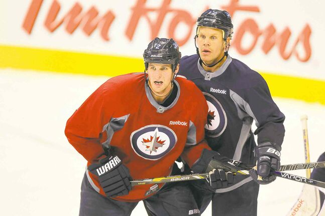 Jets defencemen Adam Pardy (left) tangles with Olli Jokinen at practice Monday. Pardy knows he has to make the most of his opportunities to stay with the big club.