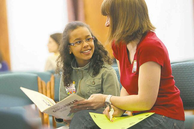 Lawyer Bev Padeanu and McKenzie Opaleke, 11, enjoy a book together.     LEFT: Lawyer Bev Padeanu and McKenzie Opaleke, 11, enjoy a book together.