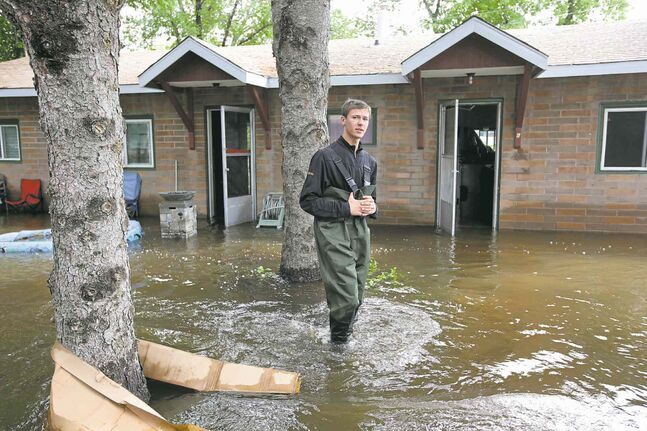 Josh Kitto walks through floodwater surrounding apartments owned by his parents in Virden Monday.