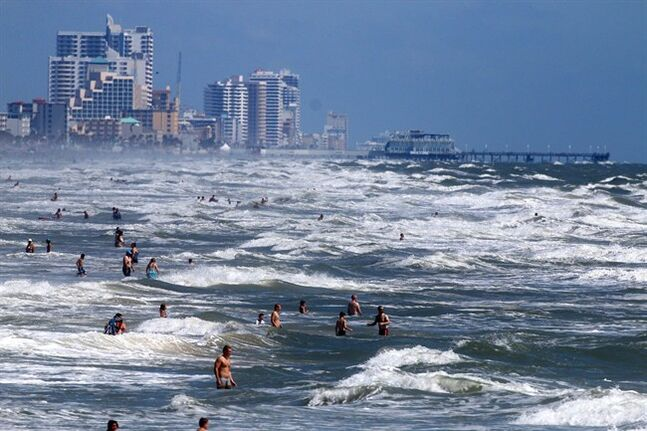 People deal with the high surf and currents off Daytona Beach generated by Tropical Storm Arthur on Tuesday, July 1, 2014. A tropical storm watch was in effect for a swath of Florida's east coast. The National Hurricane Center urged those as far north as parts of Virginia to monitor Tropical Storm Arthur's path. (AP Photo/The Daytona Beach News-Journal, Jim Tiller)