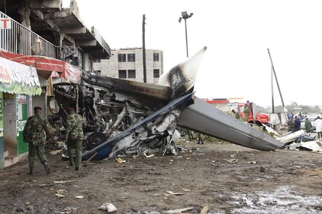 The tail section of the Fokker 50 cargo plane after it crashed into a building on take-off at Kenyatta International Airport, in Nairobi, Kenya, Wednesday, July 2, 2014. According to a police official said Joseph Ngisa, the airport's head of police investigations, four people aboard the plane were killed when their cargo plane crashed, transporting the mild stimulant drug known as Khat to the Somali capital of Mogadishu. (AP Photo/Khalil Senosi)