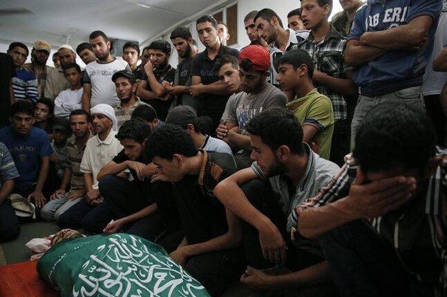 Palestinian mourners at a mosque gather around the body of Saddam Abu Muamer, who was killed in an overnight Israeli missile strike at his house on the outskirts of the town of Khan Younis, southern Gaza Strip, Monday, July 14, 2014. Saddam's wife, Hanadi, 27, and his father Mousa Abu Muamer, were also killed in the attack. (AP Photo/Lefteris Pitarakis)