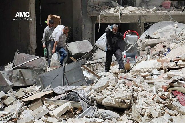 This photo provided by the anti-government activist group Aleppo Media Center (AMC), which has been authenticated based on its contents and other AP reporting, shows Syrian people carry their belongings from a building that was hit by Syrian government airstrike in Aleppo , in Aleppo, Syria, Monday, April 28, 2014. Dozens of people were killed and wounded in fighting between pro-Assad forces and rebels in the northern city of Aleppo on Sunday, reported the Britain-based Syrian Observatory for Human Rights. The fight for Aleppo is particularly important now, with analysts saying they expect Assad's forces will try wrest as much of the city as possible before elections. (AP Photo/Aleppo Media Center AMC)