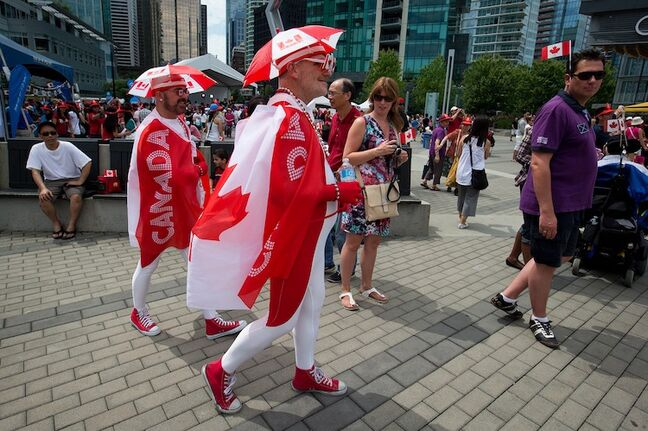 Dressed in patriotic costumes, Hugh McPherson (left) and Shawno Ashmore (centre) walk through the crowd in Vancouver, B.C.