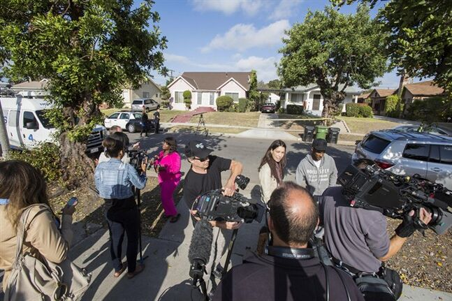Neighbors are interviewed by media in front of the home of actor Michael Jace on Tuesday, May 20, 2014, in Los Angeles. Jace, who played a police officer on the hit TV show