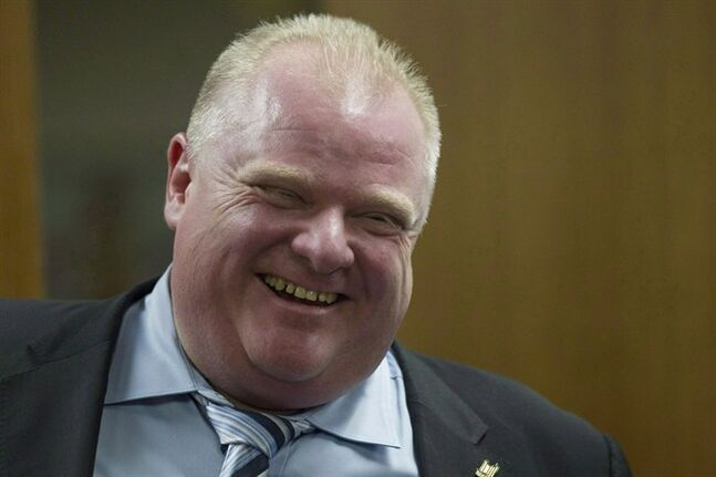 Toronto Mayor Rob Ford shares a laugh with one of his staff members outside his office at city hall in Toronto onWednesday, March 19, 2014. A stage musical is in the works about scandal-plagued Ford. THE CANADIAN PRESS/Chris Young