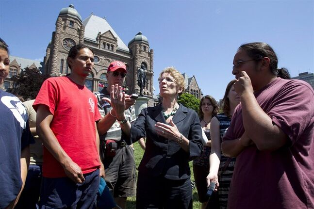 Then Ontario Aboriginal Affairs Minister Kathleen Wynne speaks with members of the Grassy Narrows band during a protest on the lawn of the Ontario Legislature in Toronto on June 6, 2012. THE CANADIAN PRESS/Frank Gunn