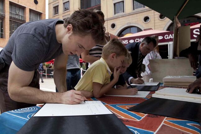 Craig Kielburger signs a book of condolences at Nelson Mandela Square in Johannesburg.