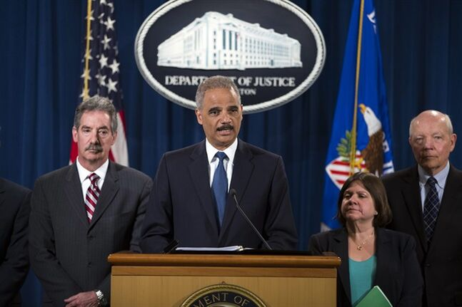 Attorney General Eric Holder, center, speaks during a news conference at the Justice Department, on Monday, May 19, 2014, in Washington. The Justice Department on Monday charged Credit Suisse AG with helping wealthy Americans avoid paying taxes through offshore accounts, and a person familiar with the matter said the European bank has agreed to pay about $2.6 billion in penalties. From left, Deputy Attorney General James Cole, Holder, Assistant Attorney General for the Tax Division Kathryn Keneally, and IRS Commissioner John Koskinen (AP Photo/ Evan Vucci)
