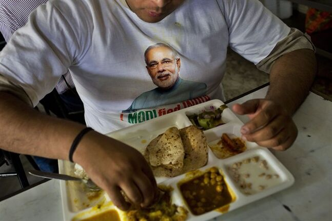 A supporter wears a t-shirt with a portrait of Bharatiya Janata Party (BJP) leader and India's next prime minister Narendra Modi and eats a meal at the canteen of the BJP party office in New Delhi, Friday, May 16, 2014. Modi and his party won national elections in a landslide Friday, preliminary results showed, driving the long-dominant Congress party out of power in the most commanding victory India has seen in more than a quarter century. Writing on banner reads