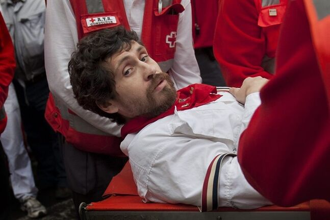 U.S. runner Bill Hillmann, 35, from Chicago, Ill., is carried on a stretcher after being gored on his right leg by a Victoriano del Rio ranch fighting bull during the running of the bulls at the San Fermin festival in Pamplona, Spain, Wednesday, July 9, 2014. A journalist and author, Hillmann, is a veteran San Fermin runner and has written many pieces about the festival. The injury was said to be serious but his life was not in any danger. Revelers from around the world arrive in Pamplona every year to take part on some of the eight days of the running of the bulls glorified by Ernest Hemingway's 1926 novel