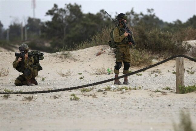 Israeli soldiers patrol along the beach front near the Israel and Gaza border on Wednesday, July 9, 2014. Israel stepped up its offensive on the Hamas-run Gaza Strip on Wednesday, pummeling scores of targets and killing more than 20 people as Israeli leaders signaled a weeks-long ground invasion could be quickly approaching. (AP Photo/Tsafrir Abayov)
