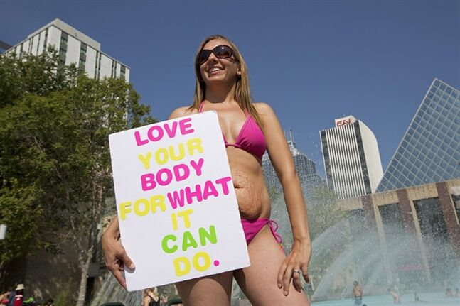 Tanis Jex-Blake, centre, takes part in a bikini protest in Edmonton on Wednesday, Aug. 6, 2014. About two dozen women pulled on bikinis in downtown Edmonton to support the mother who says she was mocked over her stretch marks. THE CANADIAN PRESS/Jason Franson