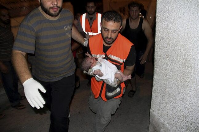 A Palestinian medic carries a wounded baby, following an Israeli airstrike on a building, at the treatment room of al Najar hospital in Rafah in the southern Gaza Strip, Thursday, Aug. 21, 2014. (AP Photo/Hatem Ali)