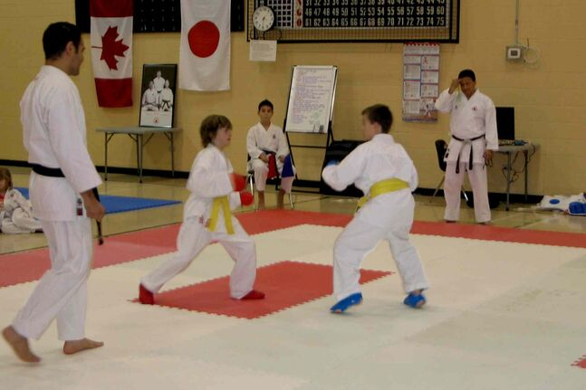 Winnipeg Open 2013 tournament comissioner Sensei Angelo Mendoza (right) looks on as students of his Bushido-Kai Canada karate school spar.